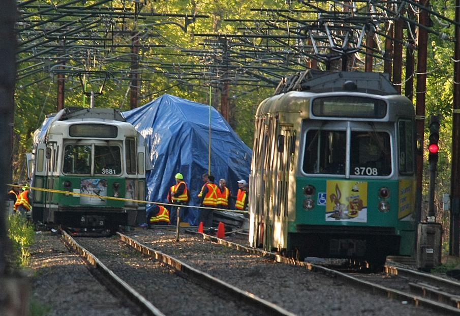 In 2008, MBTA workers survey the scene of a fatal Green Line collision. An automated system to track and control trolleys is estimated to cost $345 million to $721 million.